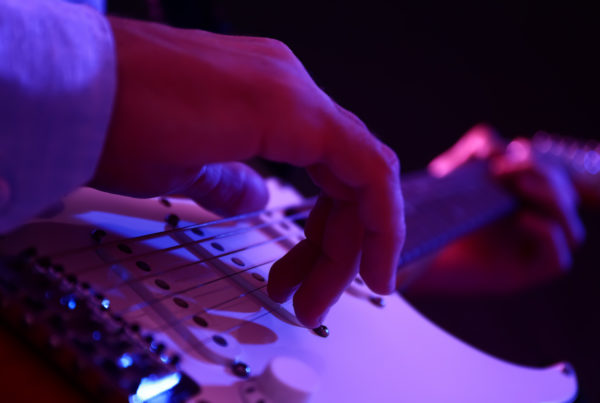 Learn to Play Music Man playing guitar, closeup view